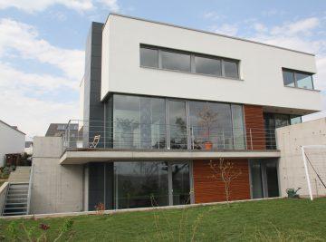 Außenansicht eines Wohnhauses mit Glasfassade und Fenstern