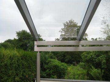 Ein Glasterrassendach vor Sträuchern