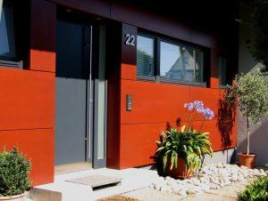 Eine graue Haustüre in einem roten Gebäude.